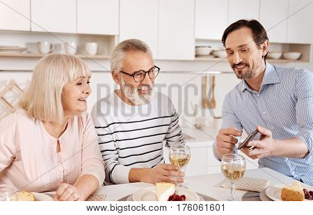 Showing photos to my parents . Joyful positive mature man having dinner and enjoying time with his aged parents while holding the gadget and showing photos