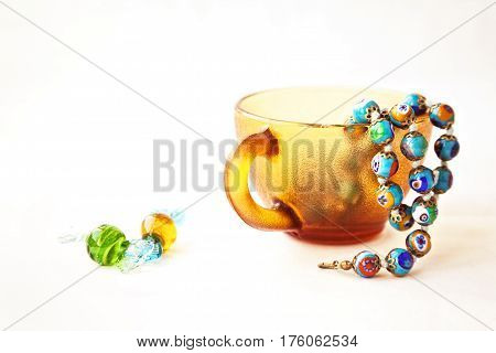 Original colorful Murano glass beads and candies. Venetian traditional millefiori necklace in a coffee cup. String of blue beads