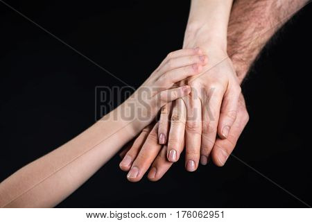 Close-up partial view of family stacking hands together on black