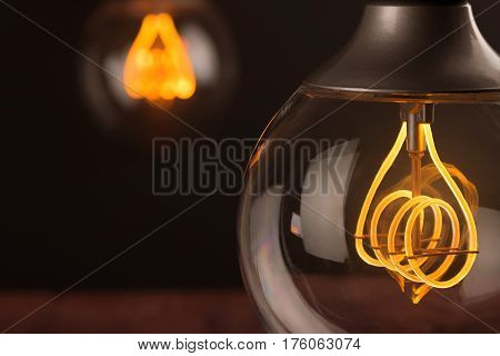 Retro Vintage Light Bulb With Led Technology Bult-in On Warm Light Yellow Tint And Black Background,