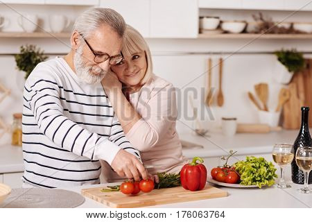 Forever loving you. Delighted harmonic beautiful aged couple standing in the kitchen and cooking healthy dinner while expressing love and hugging