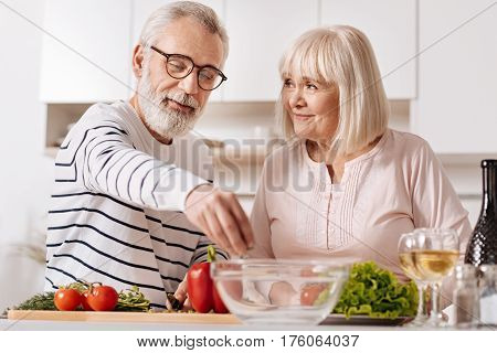 Enjoying healthy nutrition. Lively careful upbeat senior couple standing in the kitchen and cooking healthy dinner while expressing care and love