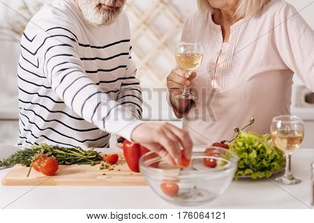 Cooking healthy dishes. Lively skillful senior couple standing in the kitchen and cooking vegetable salad while drinking wine