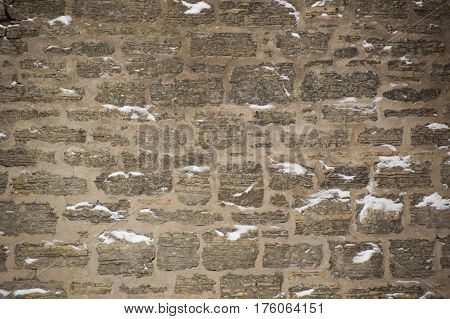 Rugged limestone wall that is uneven and covered with snow in little ledges. Strata easily seen in the rocks. Rustic and filled with cement mortar.