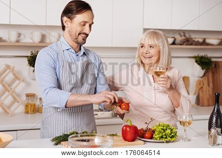 Joying healthy nutrition. Lively glad mature man standing in the kitchen and cooking vegetarian salad while his senior mother drinking wine
