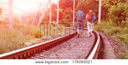 Two jolly Hikers Man and Girl in casual Travel Clothing with Backpacks walking along Railroad with back light Sun and Forest on Background