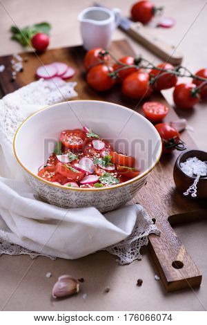 Close-up tomato salad with colorful delicious ingredients on rustic background. Bio Healthy food, herbs and spices. Organic vegetables on kitchen board.