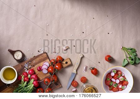 Fresh spring salad with tomatoes, radishes and spicy seasoning. Raw ingredients over rustic background with space for text. Top view. Fresh organic vegetables from garden for healthy cooking.