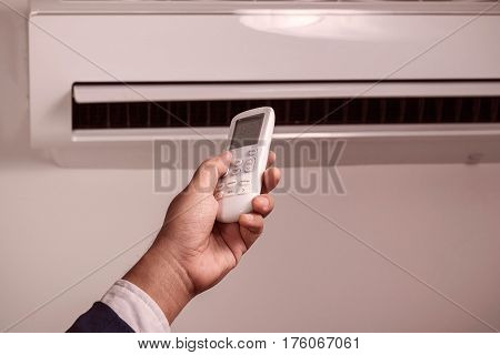 Hand was pressing the remote control to turn on the air conditioner in the office.