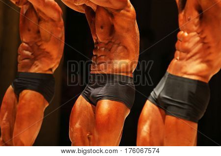 Male body builders pose showing their abdominal muscles