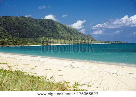 Sandy beach and turquoise green sea in front of cape in Ishigaki island