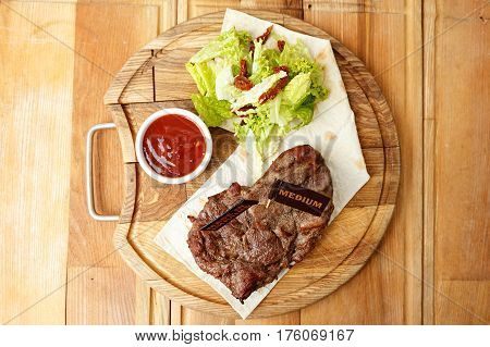 cooked steak on a pita a wooden board standing next to a gravy boat with ketchup and greens