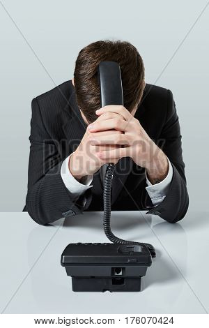 A young man in a black suit dials the phone number while sitting in the office. Manager beats himself over the head with a telephone