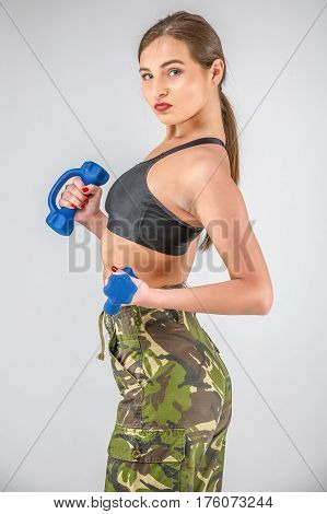 A Sporty Female Fitness Model Dressed In A Military Camouflage Holds Dumbbells.