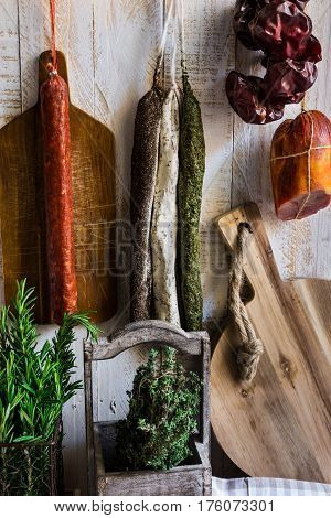 Charcuterie variety of sausages hanging on hook wood cutting board string with dry peppers fresh garden herbs Provence pantry kitchen interior