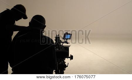Silhouette Of Working People Or Production Film Crew Are Making Movie Or Shooting.