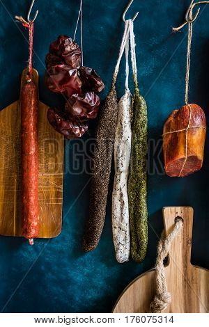 Assortment of sausages Spanish charcuterie wood cutting board dry peppers on dark blue background gourmet rustic style