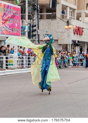 Participants At сarnival On Stilts Are Walking Along The Street