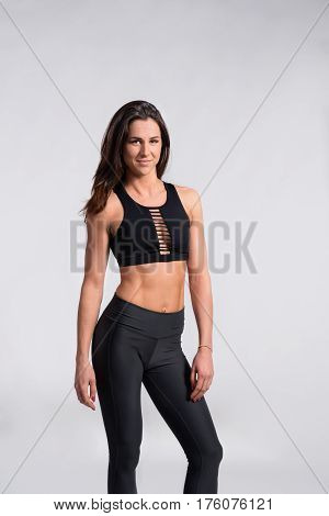 Attractive young fitness woman in black tank top and black leggings, slim waist, perfect fit female body. Studio shot on gray background.