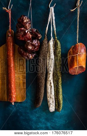 Assortment of sausages Spanish charcuterie wood cutting board string with dry peppers on dark blue background gourmet rustic pantry