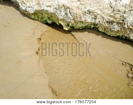 Freshwater river on the beach that flows into the sea