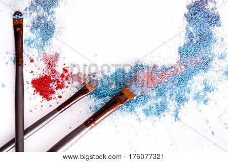 Makeup brushes frame with blush and eyeshadow of pink, blue and coral tones sprinkled on white. Make up and female cosmetics background