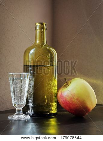 Vintage shot glass Bottle and Ripe Apple on a table. Retro style still life.