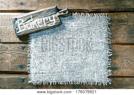 Vertical frame of white burlap on rough pine wood boards. Wooden cutting board with text 'Bakery' as title bar. Structured natural style background