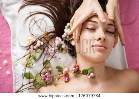 Top view of young beutiful woman at spa lying with tender flowers white facial massage