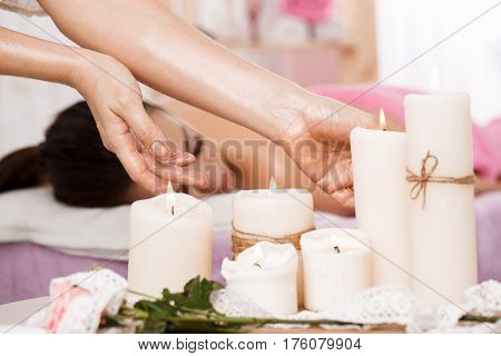 Beauty and body care concept. Young pretty woman on massage couch. Massuer taking candles