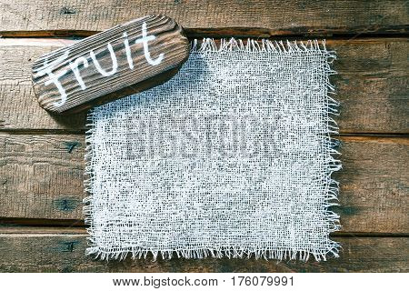 Vertical frame of white burlap on rough pine wood boards. Wooden tablet with text 'Fruit' as title bar. Structured natural style background