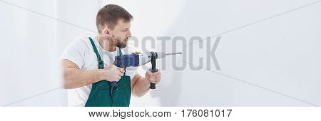 Man with professional electric drill making holes in wall panorama