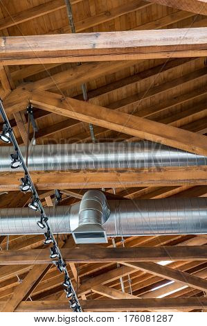 Ductwork and lights below a natural wood roof and rafters