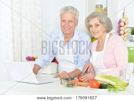 Beautiful elderly couple preparing breakfast with laptop