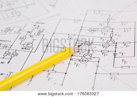 Electronics and Engineering. Pencil on printed drawings of electrical circuits