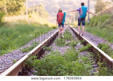 Old Railroad verdurous with green Summer Grass and wild Flowers and Silhouettes of two Hikers Man and Woman with Backpacks on Background Focus on Grass, bodies are blurred