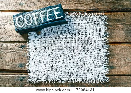 Vertical frame of white burlap on rough pine wood boards. Wooden tablet with text 'Coffee' as title bar. Structured natural style background