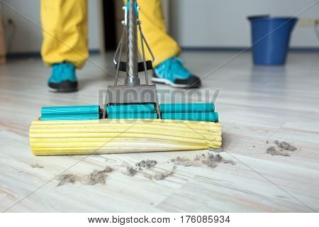 Person in professional uniform yellow pants blue shoes cleaning wooden floor with with brush mop in home of modern office interior close up of cleaner brush.