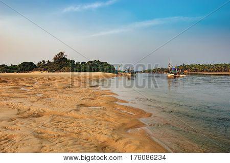 Goa, India - November 15, 2012: Tropical Betul Beach with fishing boats at Sal River, South Goa, India. Sand dunes on the beach