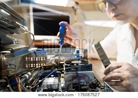 Throw the Window image of Computer Technician working with Hardware using tools in natural tones