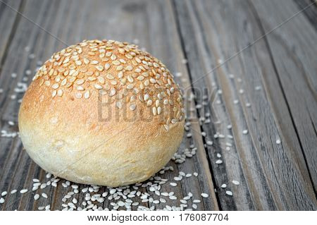 Bun with sesame seeds on wooden table