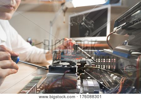 Throw the Window image of Computer Technician working with Hardware using tools