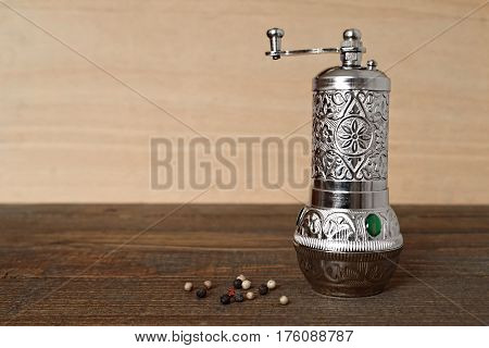 Pepper mill and peppercorn on wooden background