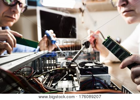 Male and female Computer Technicians working with Hardware using tools including incandescent soldering iron with smoke in Service Workshop