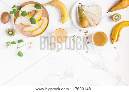 Fresh smoothie with pear banana melon kiwi. Summer fruit cocktail on white table. Vegan vegetarian detox dieting concept. Flat lay top view