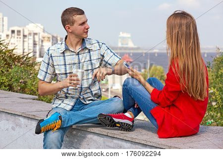Young Woman enjoying downtown view sitting on stone parapet