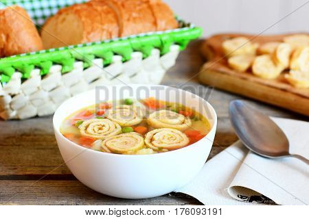 Delicious soup with vegetable mix and fried omelette in a bowl. Bread slices, spoon on a rustic wooden background. Healthy soup with omelette, carrot, peas, leek, cauliflower and potatoes