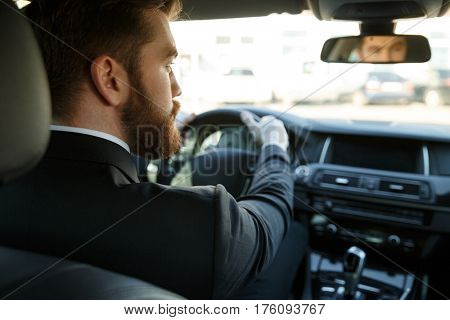 Back view of young male driver holding steering wheel