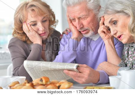 Portrait of three elderly people having breakfast and reading a newspaper