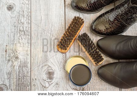 Women's shoes and care products for footwear on a gray wooden floor.